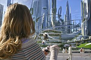 woman looking out at a futuristic cityscape
