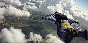 image of person in base-jumping suit over clouds